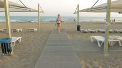 Woman in bikini going among sunbeds and sunshades Stock Footage