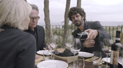 Parents with grown-up son dining outdoors Stock Footage