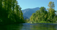 A dolly shot, heading down a river in Bella Coola. Blue mountains are seen in th Stock Footage