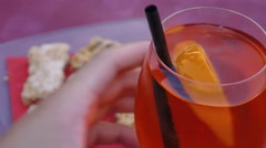 Man stirs spritz aperitivo, drinks it and puts it back on table Stock Footage