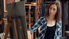 Young woman painting a canvas in a studio Stock Footage