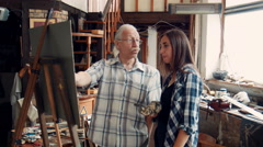 Aged teacher painter, painting with young girl Stock Footage