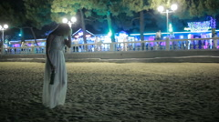 Girl walking on the beach. drinking wine. Night resort. woman in white dress Stock Footage