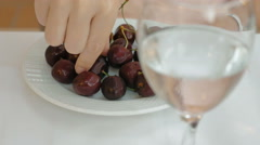 Sweet cherry with glass of water in foreground Stock Footage