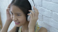 4K : Attractive Asian girl listening music by headphone in the room Stock Footage