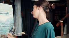 Portrait of young woman painting a canvas in a studio Stock Footage