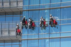 Group of window cleaners suspended from cables Stock Photos