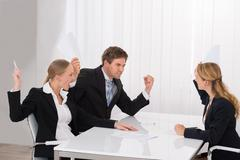 Displeased Young Businesspeople Having Argument At Workplace Stock Photos