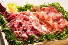Salami cold cuts in box surrounded with greens Stock Photos