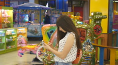 Young woman playing Pokemon GO indoor at shopping center, using smart phone Stock Footage