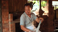 Balinese cook grating coconut into big clay bowl Stock Footage
