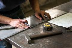 Metalworker marking measurements on metal Stock Photos