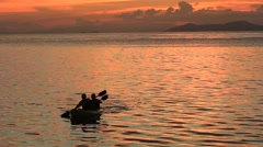 Fisherman paddle boat home at sunset Stock Footage