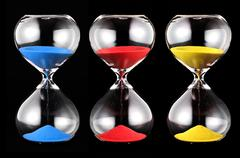 Three hourglasses with colorful sand Stock Photos