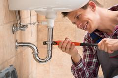 Smiling Male Plumber Fixing Sink Pipe With Adjustable Wrench In Bathroom - stock photo