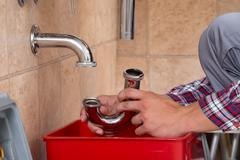 Close-up Of Plumber's Hand Fixing Sink In Bathroom Stock Photos