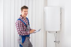 Young Male Plumber Holding Clipboard Checking Electric Boiler Stock Photos