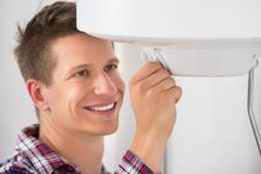 Smiling Young Male Plumber Adjusting Temperature Of Electric Boiler Stock Photos