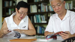 Asian senior couple reading books and magazines learning and study concept - stock footage