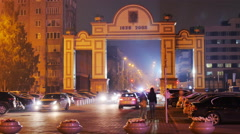 Intense car traffic in the night city, pedestrians, arch Stock Footage