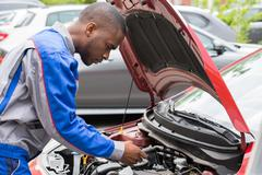 Close-up Of Male Mechanic Checking Car Battery Level With Multimeter Stock Photos