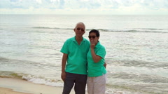 Asian senior couple stand at the beach at looking to ocean Stock Footage