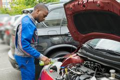 Young African Mechanic Pouring Oil Lubricant Into The Car Engine Stock Photos