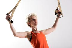 Strong woman pulling fitness cords - stock photo
