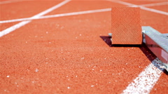 Single track and field sprinter in a stadium starting out of the block - stock footage