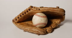 Throwing Baseball into Old Mitt Remembering the Game on White, 4K Stock Footage