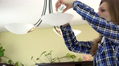Serious housewife woman changing light bulbs - stock footage