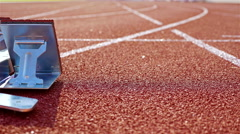 Single track and field sprinter in a stadium starting out of the block Stock Footage
