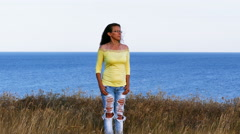4K. Adult woman in yellow blouse  stand  on seashore. Summer day Stock Footage