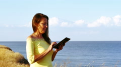 4K. Adult woman in yellow blouse works with  tablet on seashore  Summer day Stock Footage