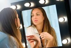 Young woman admiring herself in the mirror Stock Photos