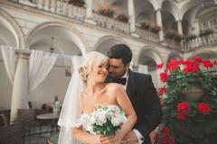 Portrait of happy newly wedding couple with bouquet - stock photo