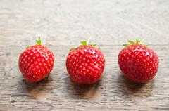 Strawberries alignment on wooden table background Stock Photos