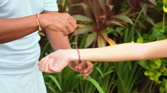 "Shaman ties ""tri dhatu"" string bracelet on woman's wrist, Bali Stock Footage"