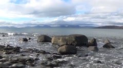 Tracking shot of waves and rocks on the shore of the Sound of Jura Stock Footage