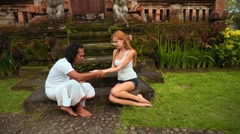 Balinese shaman performs palm reading for european woman Stock Footage