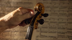 Tuning a violin. Close up shot with musical notes on background Stock Footage