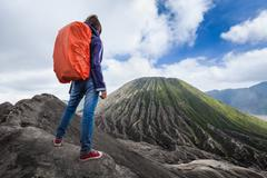 Backpacker standing on an edge of volcano crater Stock Photos
