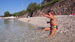 Kid throws a handful of pebbles into the sea Stock Footage