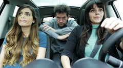 Two women one man in car making funny crazy faces slow motion Stock Footage