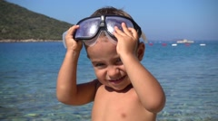 Kid takes off goggles and looks into camera Stock Footage