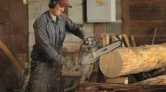 Motor chainsaw cutting wooden beam. Man work with wood house Stock Footage