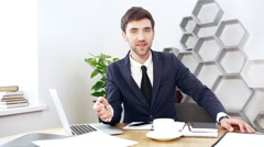 Young successful businessman speaking, sitting at his workplace in office. Slow Stock Footage