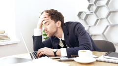Young successful businessman working at laptop, falling asleep in office. Slow Stock Footage