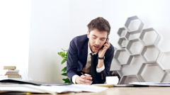 Young successful businessman rummaging in papers, speaking on phone at his Stock Footage