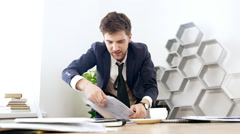 Young successful businessman rummaging in papers at his workplace in office Stock Footage